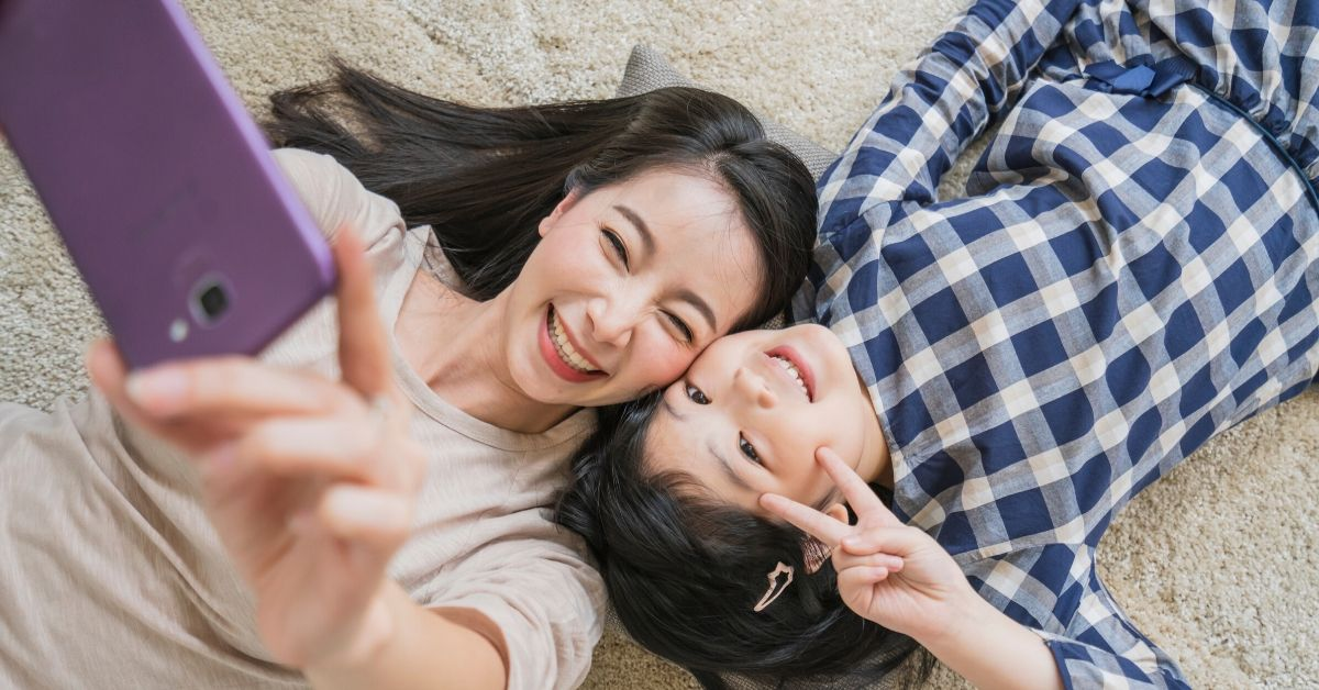 Ting Review - picture of mother and daughter taking selfie laying down