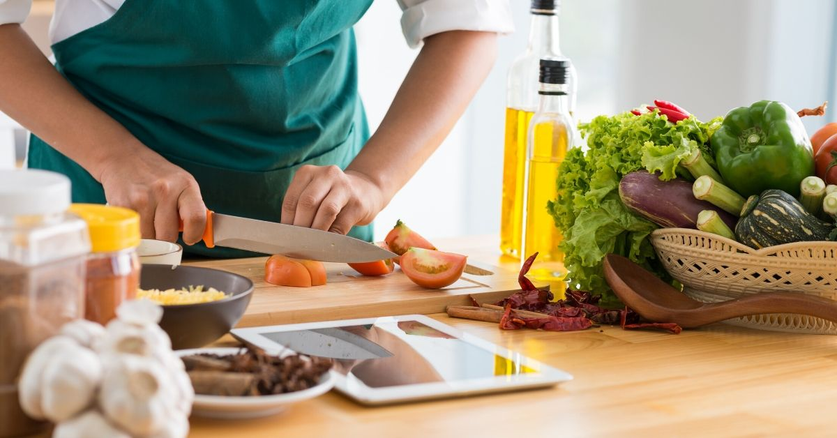 Things I HATED About Blue Apron - picture of someone using cutting board with produce and tablet next to them