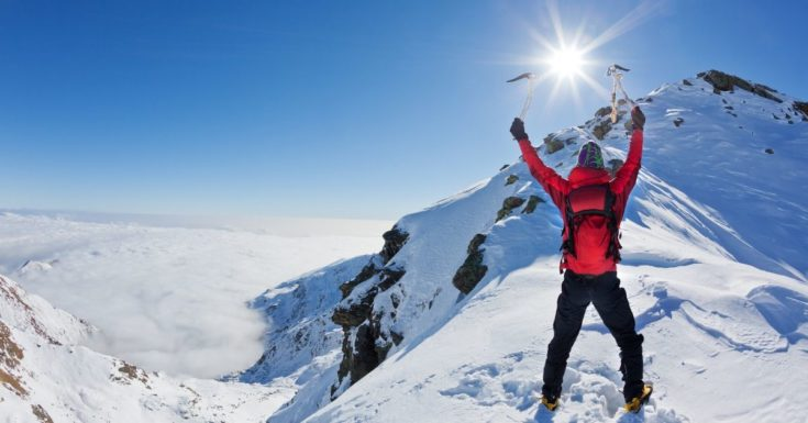 Debt snowball - picture of man celebrating at top of snowy mountain