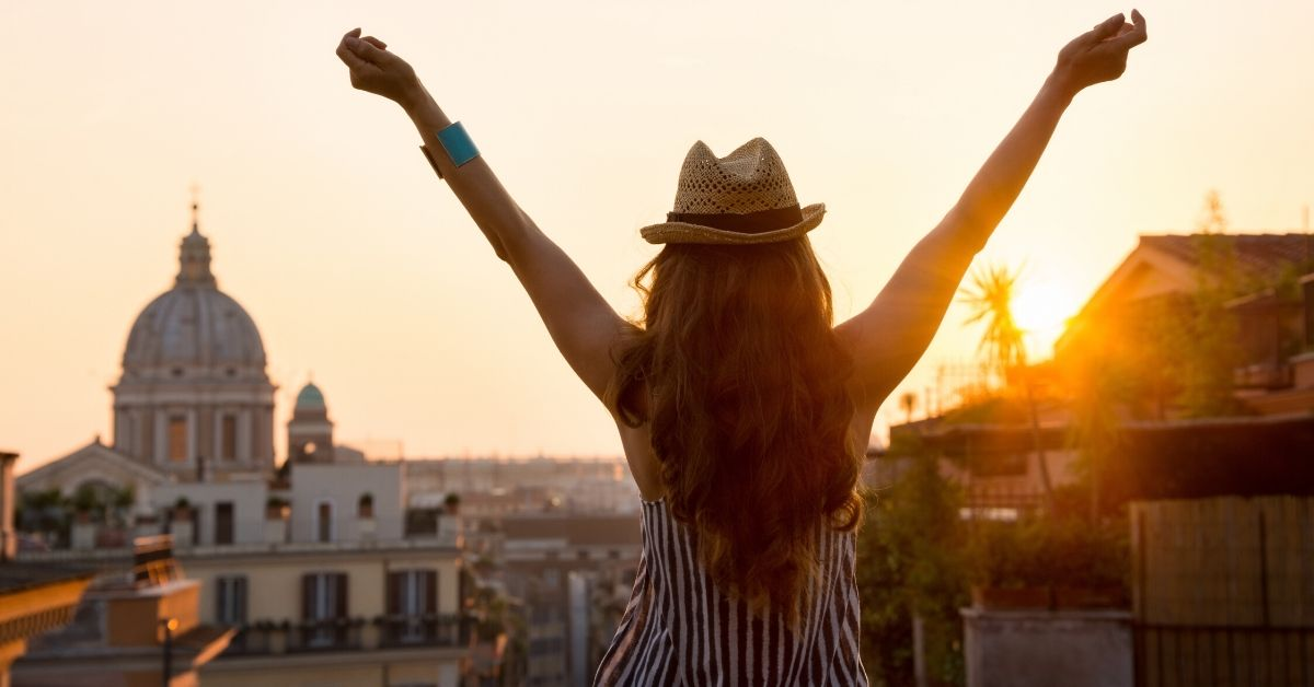 Reasons Being Frugal is Awesome - picture of back of woman with hands raised overlooking rome