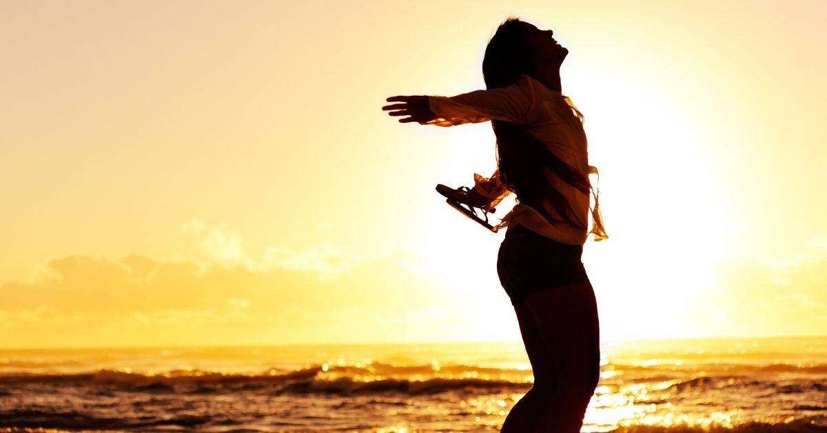 5 Ways to Crush Budget - picture of silhouette of woman dancing on beach