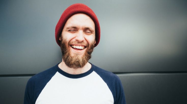 image of bearded man in stocking hat who is laughing