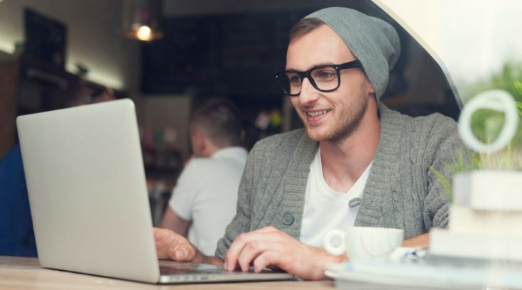 image of young man in glasses working on computer