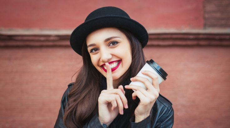 Image of smiling young woman in black bowler hat holding a coffee cup and motioning to be quiet.