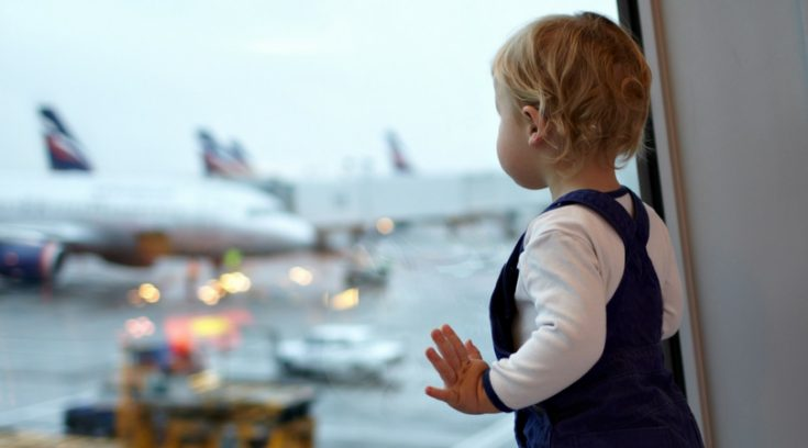 toddler looking out window at airplanes