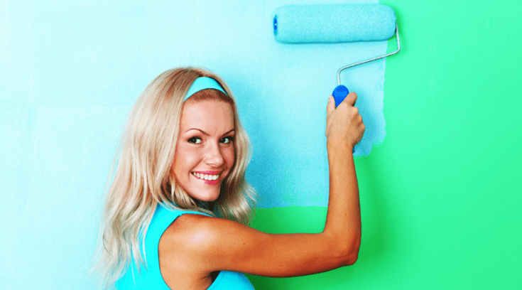 smiling woman painting a wall blue as a work-from-home jobs