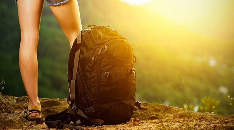 woman on mountain with travel backpack