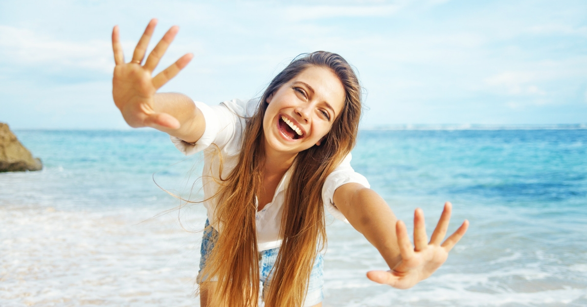 How I Saved Six Figures in my 20s - picture of joyful woman on beach