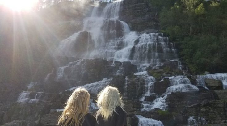 Photo of two children looking at beautiful cascading waterfall