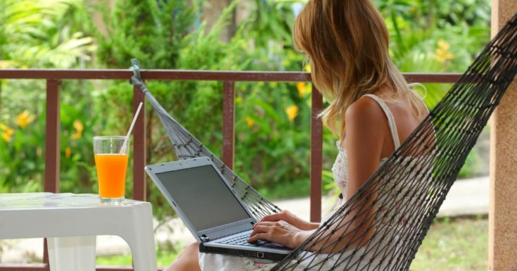 Picture of woman working on laptop in hammock