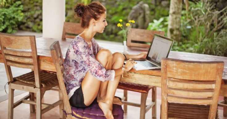 Using Passive Income to Dream Big and Travel More - picture of woman sitting on porch with laptop