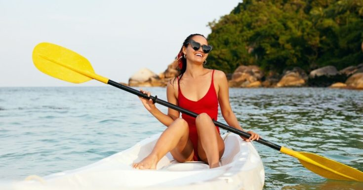 Amex Gold vs. Amex Platinum - young woman in kayak