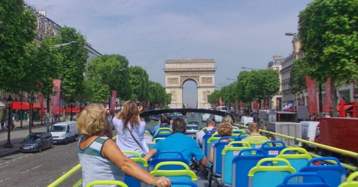 Photo of people on open air bus looking at Arc de Triomphe in Paris
