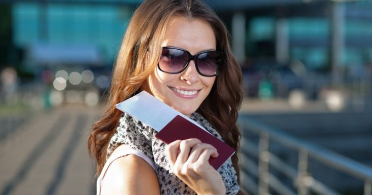 REAL ID Review - picture of young woman holding up passport and smiling