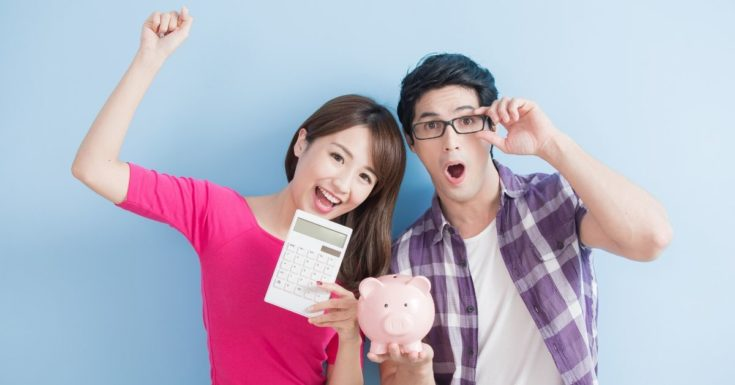 Personal Loan vs Balance Transfer Credit Card - picture of young couple with calculator and piggy bank celebrating