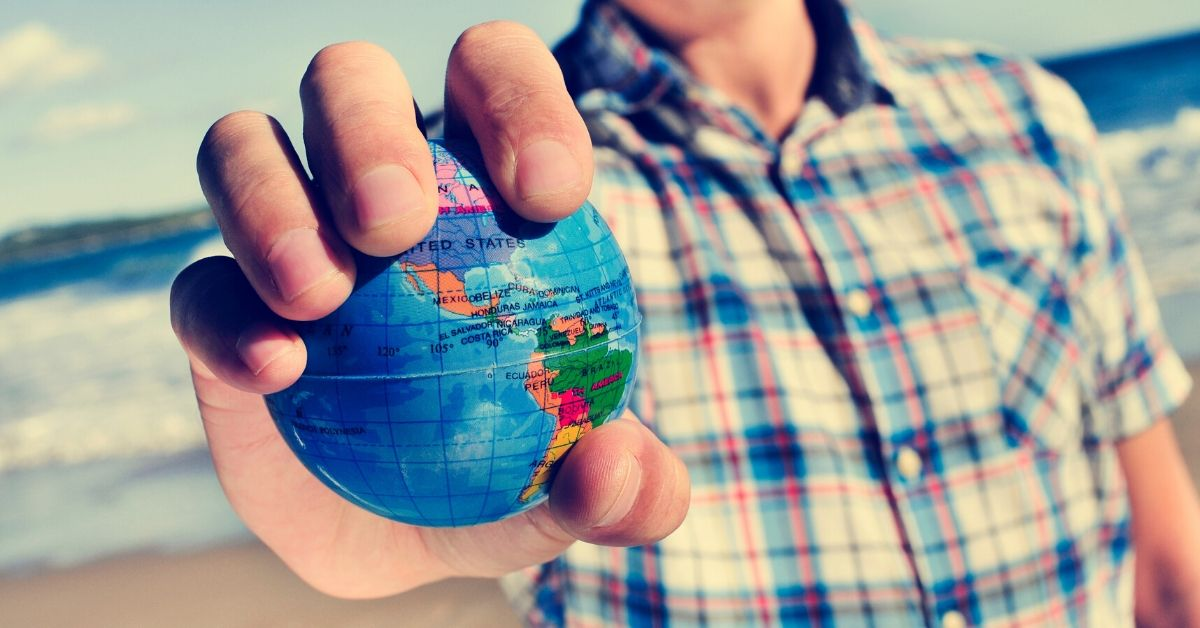 How to Get a U.S. Passport - close up of man holding globe in his hand at beach