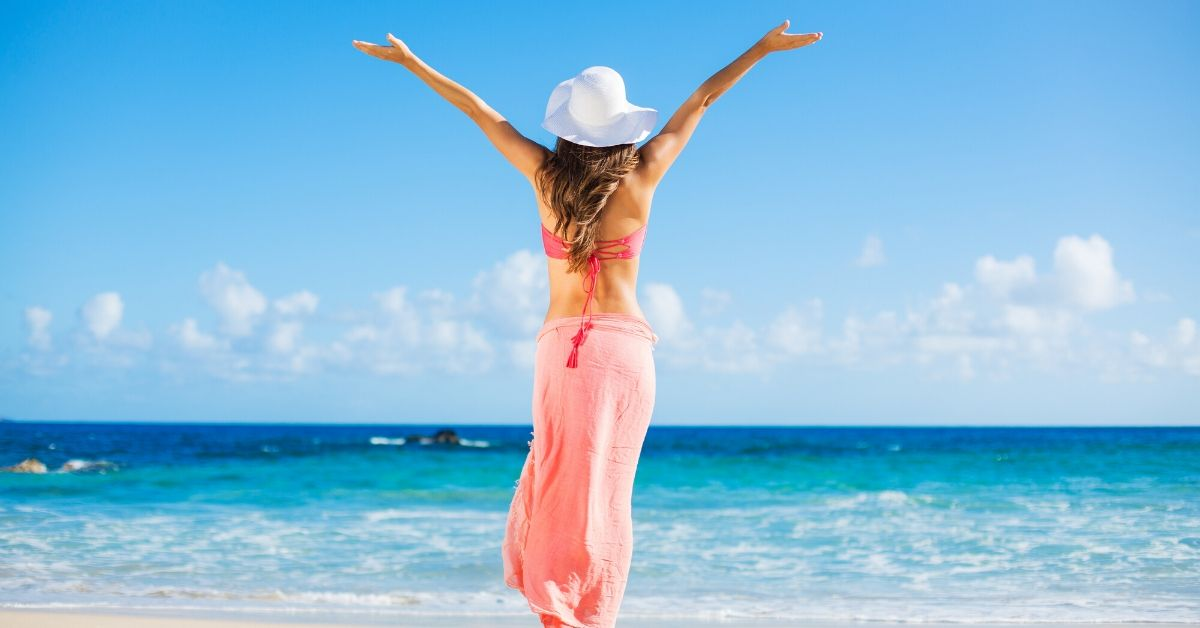 Types of Credit Cards to Fit Your Needs - picture of back of woman with arms raised staring out at ocean