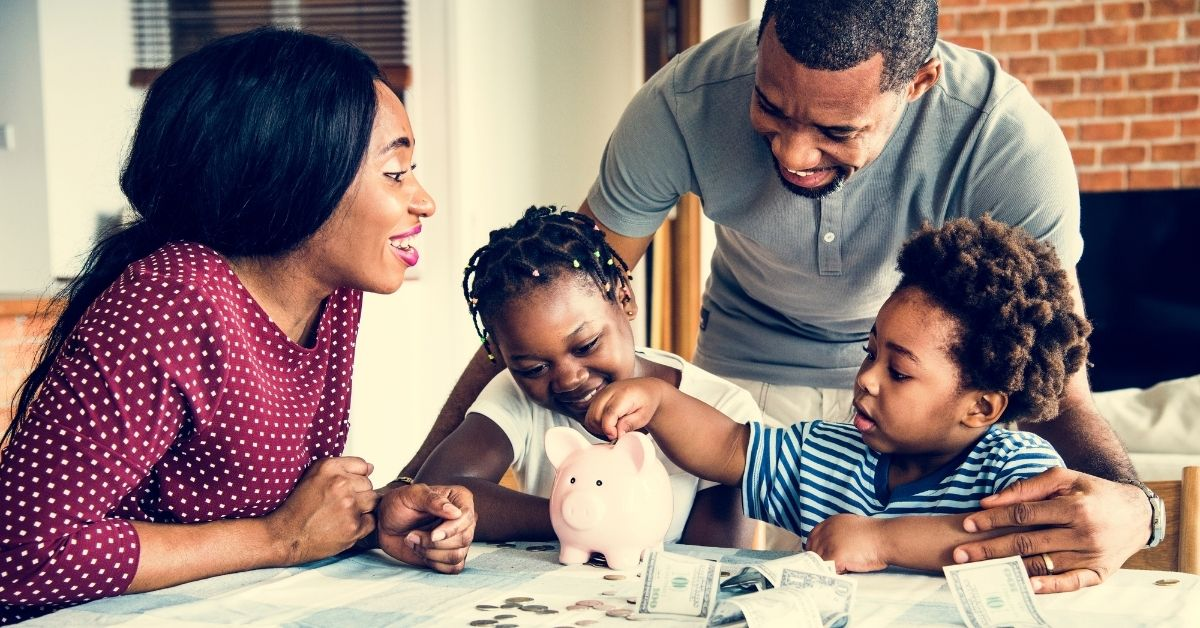 4 Easy and Practical Ways to Raise Money-Smart Kids_picture of Black family at table with piggy bank and money