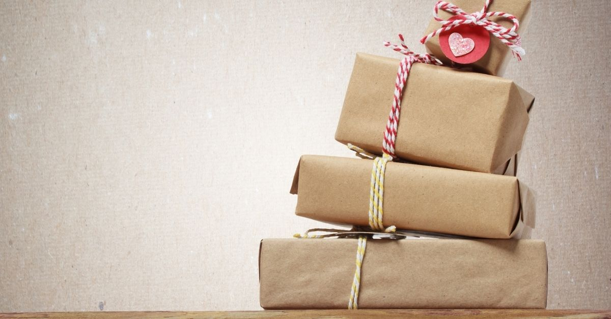 Tips Keep Holiday Spending in Check - picture of hand-wrapped tower of gifts falling over