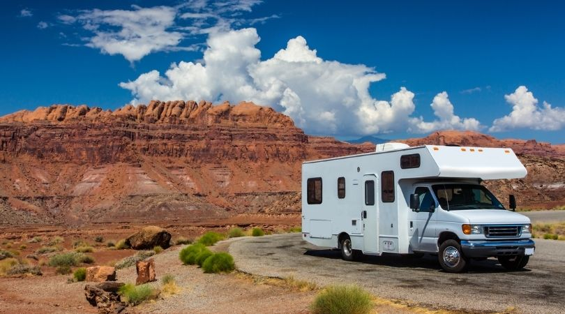 image of RV on road with desert landscape