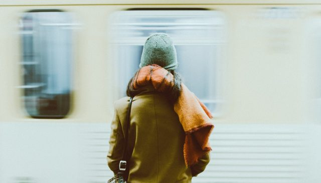 time lapse photography of person standing near train