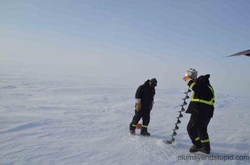 Drilling down into the ice with an auger