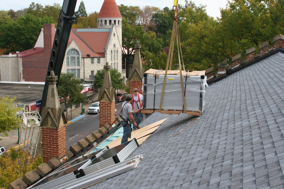 solar-panels-being-lifted-ont-the-roof