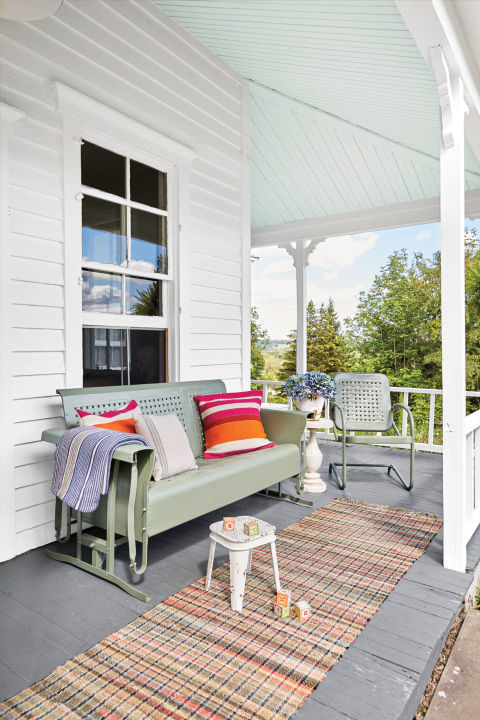 All this renovated New York home's expansive porch needed to take it from scary to airy was new flooring and a fresh coat of paint. Inspired by a superstition that a light blue ceiling would repel bees, the owner painted it a soft blue-green shade.