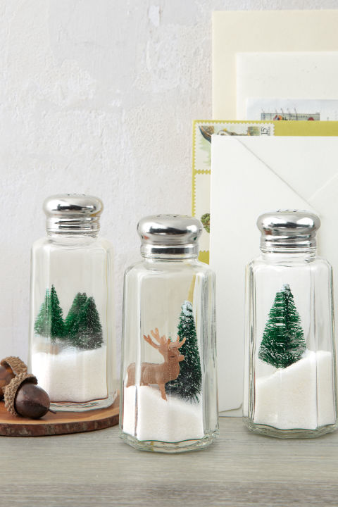 Here's one Yuletide idea that's definitely worth its salt: Turn under-a-dollar shakers into mini winter wonderlands by nesting toy evergreens and deer atop iodized