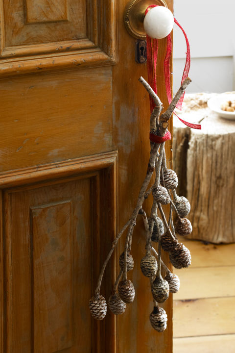 Pine branches decorate a door stripped to bare wood in this Wisconsin home. What you'll need: ribbon ($6, amazon.com); pinecones ($8, amazon.com)