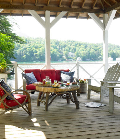 Adirondack chairs and midcentury bentwood seating, as well as a coffee table crafted by a local artisan, furnish this summer cabin's deck. The blue-and-white pillows are from Restoration Hardware.