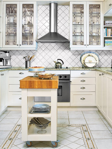 Pattern plays its many-faceted part in an all-white kitchen. A mosaic border frames porcelain floor tiles, and echoes the designs of the leaded-glass cabinetry and the backsplash. RELATED: 10 Ways to Decorate With White