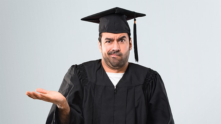 Bearded man in a graduation robe shrugging with an unsure look on his face