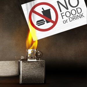 lighter setting a no food or drink sign on fire