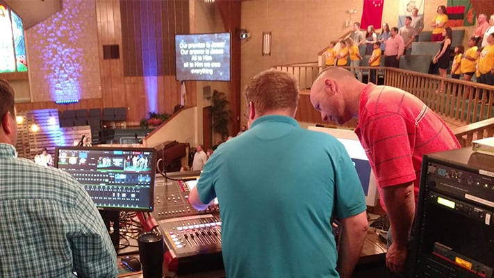 2 men standing over a new sound board. One man is showing how to operate it