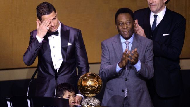 Cristiano Ronaldo wipes away the tears after Pele (right) presented him with the trophy