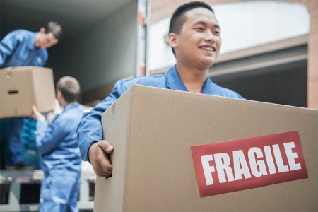 Happy movers carefully unloading your fragile items from the moving truck