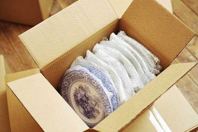 Fragile china collection meticulously wrapped in bubblewrap inside a premium cardboard box