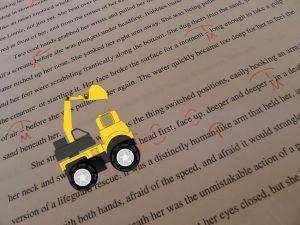 Backhoe cartoon drives across edited manuscript