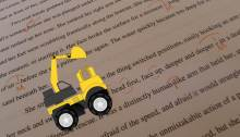 Backhoe cartoon drives across edited manuscript