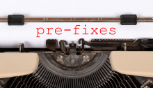 "Closeup of a sheet of paper in a typewriter with the word ""pre-fixes"" (with a hyphen) in red"
