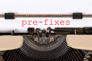 "Closeup of a typewriter. On an otherwise blank sheet of paper is the word ""pre-fixes"" (with a hyphen) in a red typewriter font."