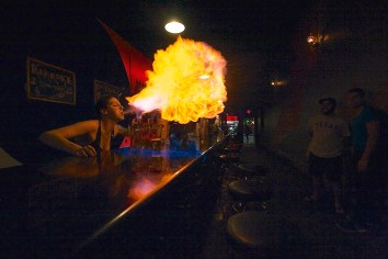 """James Healy, University of Minnesota (Liam James Doyle, adviser) Bartender Hannah Hollibaugh prepares a round of Flaming Dr. Peppers, an Austin staple, at Big Bang Bar on Thursday night. After eleven years of bartending in Austin, the explosive drinks are just part of the job. """"The hardest part is getting everyone to stand back far enough,"""" Hollibaugh said."""