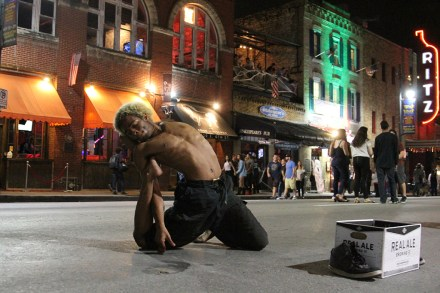 """Rebecca M. Dietrich, Slippery Rock Univeristy (Mark Zeltner), adviser) A contortionist performs in the middle of 6th Street for Austin's night life. The town was covered with party goers dressed up for Halloween as the contortionist performed. The man goes by the """"The 6th Street Snake."""""""