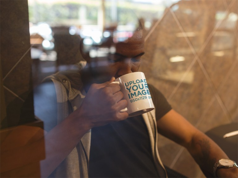 Young Man at a Coffee Shop Drinking from His Mug Mockup