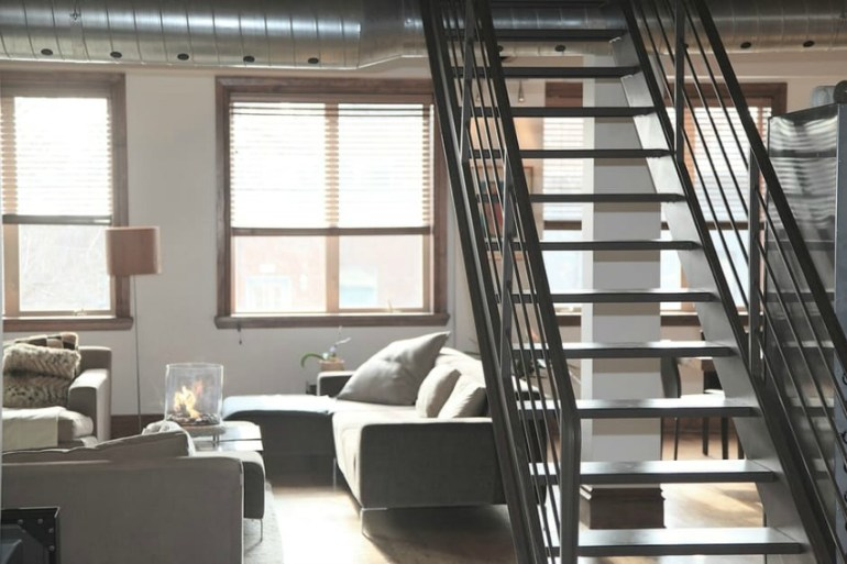 Image is of stairs inside of a home and the image shows a different angle of the picture being taken Photo by Life of Pix