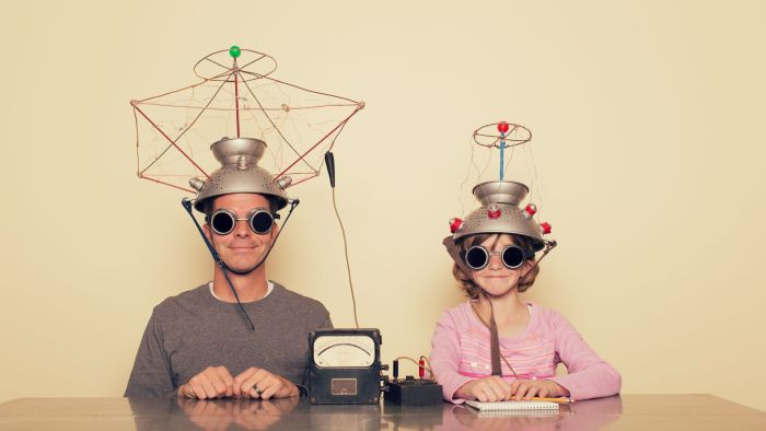 Parent and child wearing metal hats and doing a science experiment