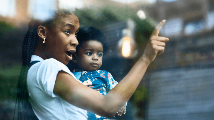 Woman holding baby and pointing at something out the window effective communication