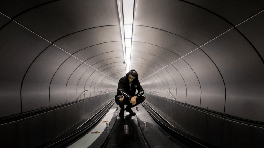 Young man squatting in a tunnel