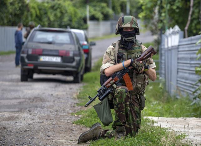 A Ukrainian soldier pulls security